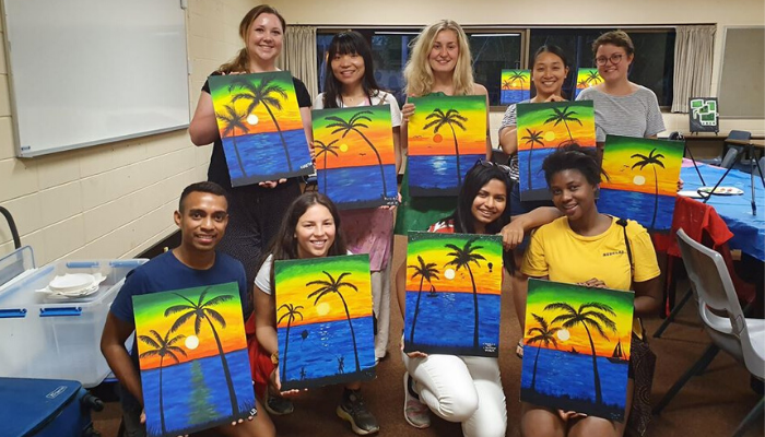 Students with painting of Darwin sunset