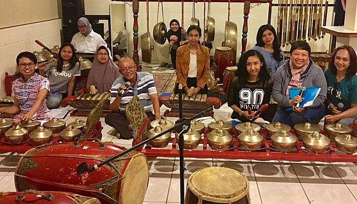 CDU student Dina Widyaputri Kariodimedjo and her research peers sit amongst Indonesian cultural artefacts