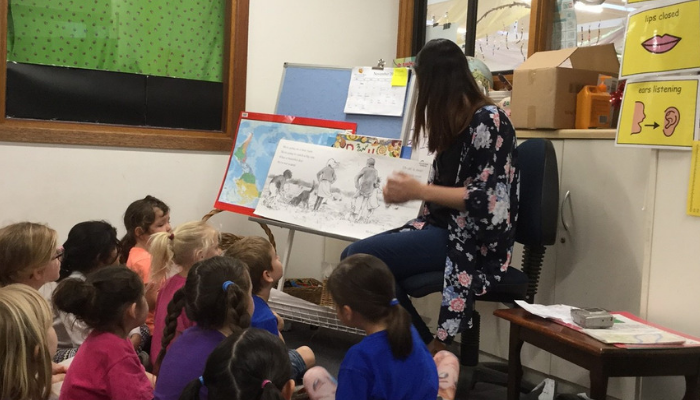 Sallie reading a book to the kids in her classroom