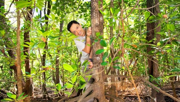 CDU student Sigit Sasmito smiling from behind a tree