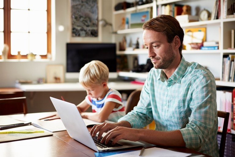 Man studying at home with kid