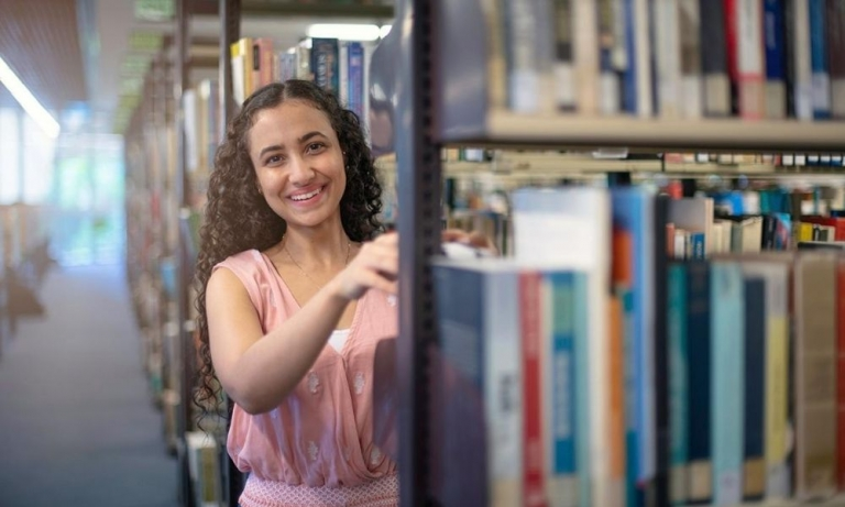 CDU student Nancy Soliman in the library choosing a book.