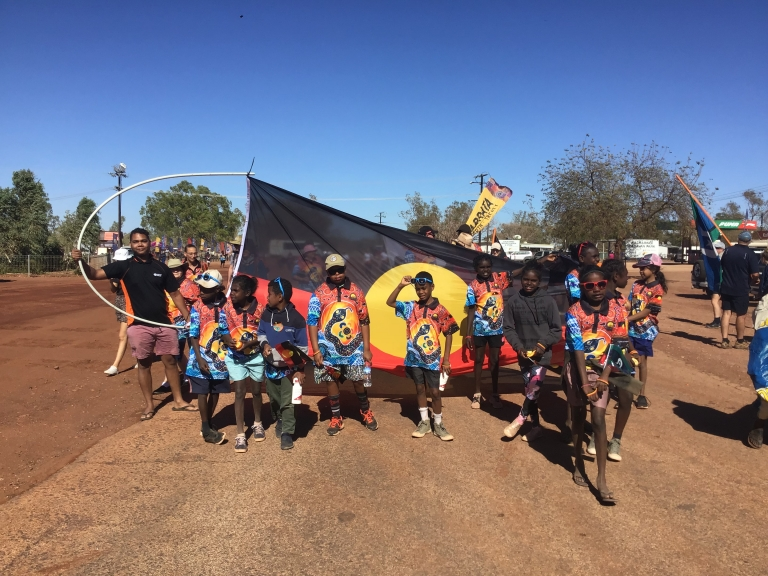 Luke with a group of young children smiling while holding the Aboriginal flag