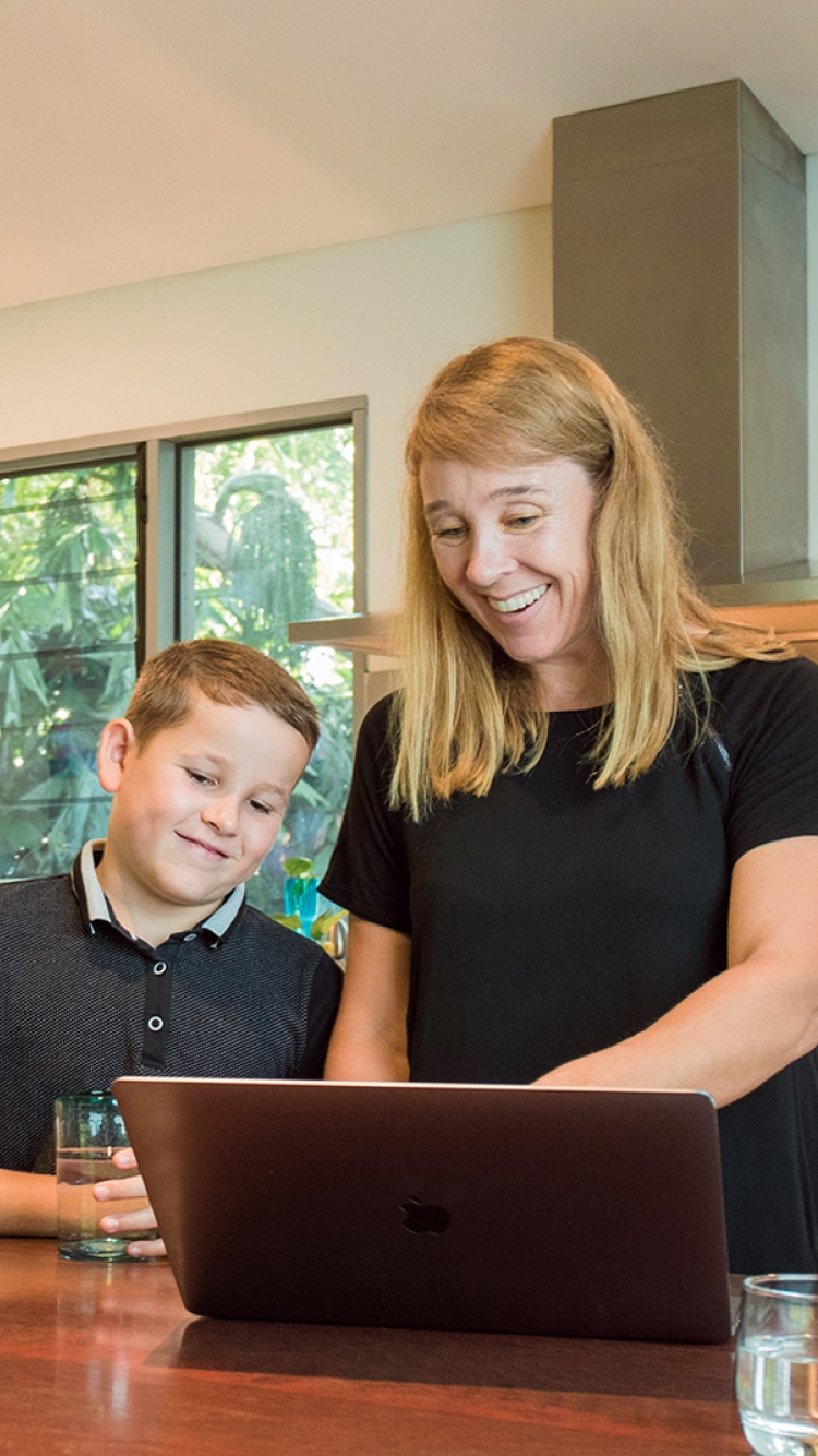 Mother and son looking at laptop in kitchen