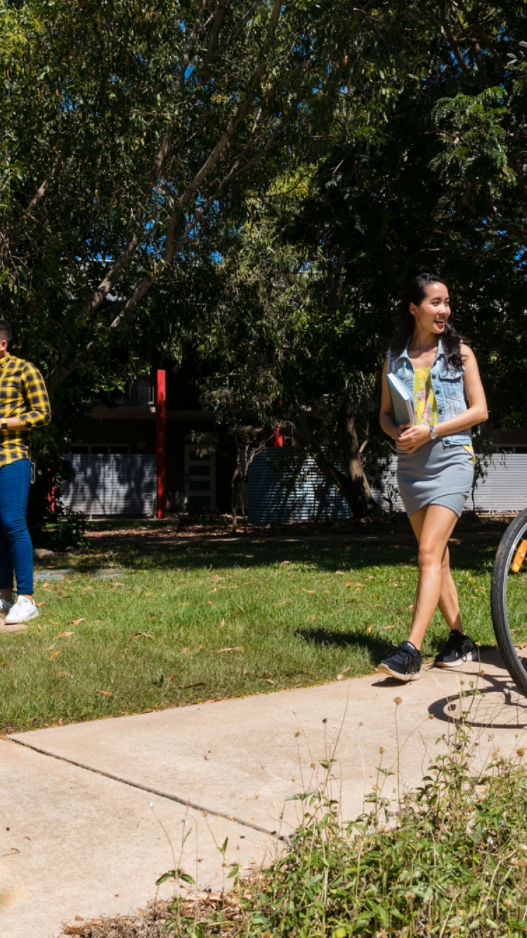 Two female students walking their bikes and smiling