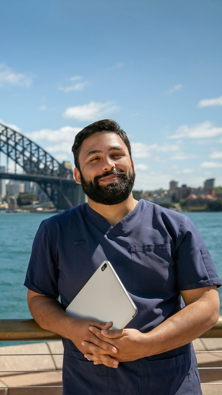 CDU nursing student in front of the Sydney Harbour Bridge holding a laptop