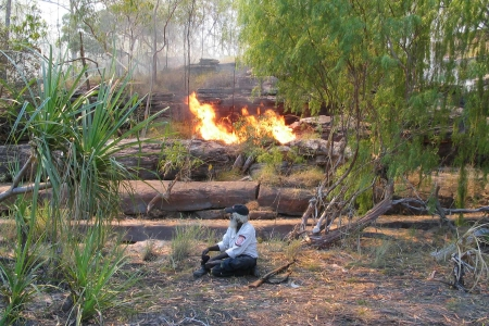 Indigenous ranger in front of fire in the bush