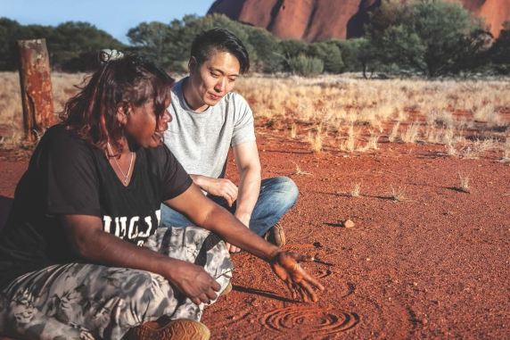 Indigenous woman explaining a figure drawn in the dirt to a man who is sitting with her and listening