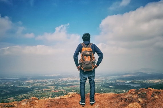 Male traveller with backpack overlooking a mountain view