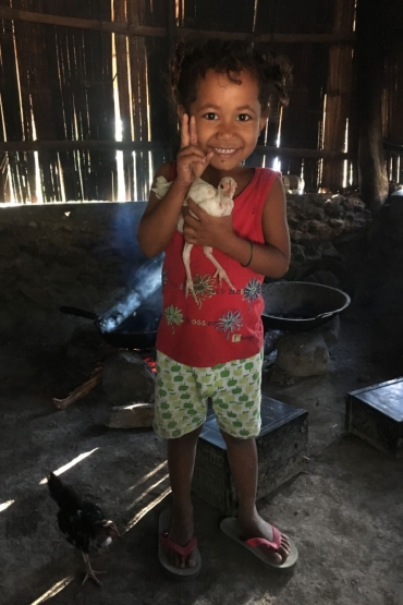 A child holding a chicken inside a building