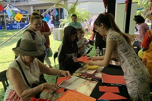 Visitors learn how to do paper cutting
