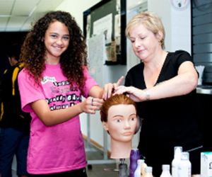Linda Manning (right) shows student Haylee McLean how to make a bun. Photo: Kate Freestone
