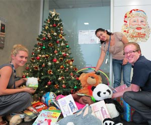 Sarah Lockett, Lyse Wang and Baden Jones of the Human Resource Services team at Casuarina campus place donated gifts under the Christmas giving tree