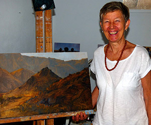 """Ms Taylor with one of the landscapes in the """"Portraits of Country"""" exhibition"""