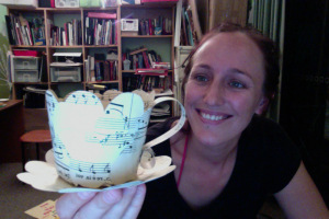 Jo Green with one of the paper tea cups from the AfterLife Dialogues exhibition