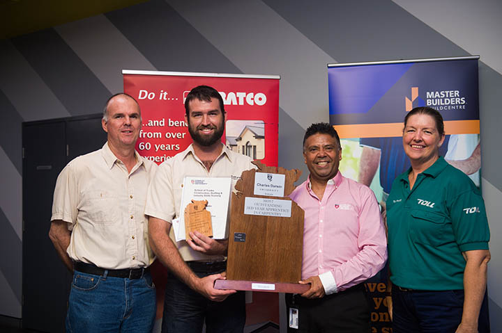 Most Outstanding Third Year Apprentice in Certificate III in Carpentry Tennyson Curtis receives his major prize and perpetual trophy from CDU Team Leader Luis Espinoza, flanked by Tennyson's family