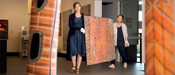 CDU Art Gallery curator Kellie Joswig and Collection and Exhibitions Officer Eileen Lim with the newly acquired Four Dreamings painting by Central Desert artist Carbiene McDonald Tjangala