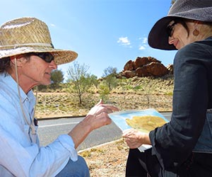 Arts trainer Henry Smith makes a technical observation in a student's water colour work of Dog Rock