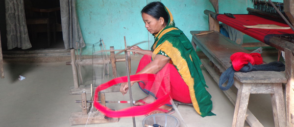 A woman spins yarn to use on her hand loom – a traditional industry that may be under threat in Bangladesh