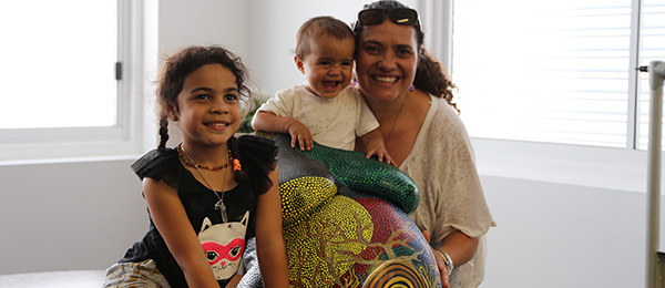 Participant and midwife in the Birthing in Our Community program in Brisbane's southern suburbs, Kyleigh Brown-Lolohea, with her daughters and belly cast made during her pregnancy