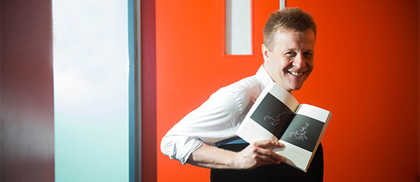 Dr Christian Bok with his book The Xenotext: Book 1