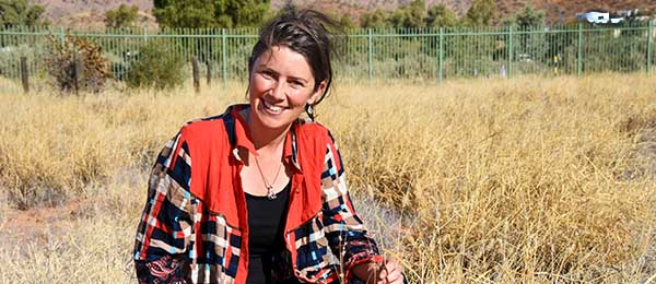 PhD candidate Ellen Ryan-Colton examining how buffel grass is changing the arid landscape. Image: Patrick Nelson
