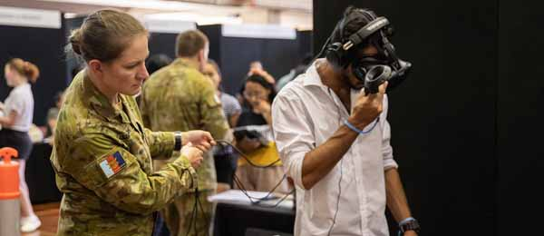 A defence recruitment staffer demonstrates to a student technology that is used in the military