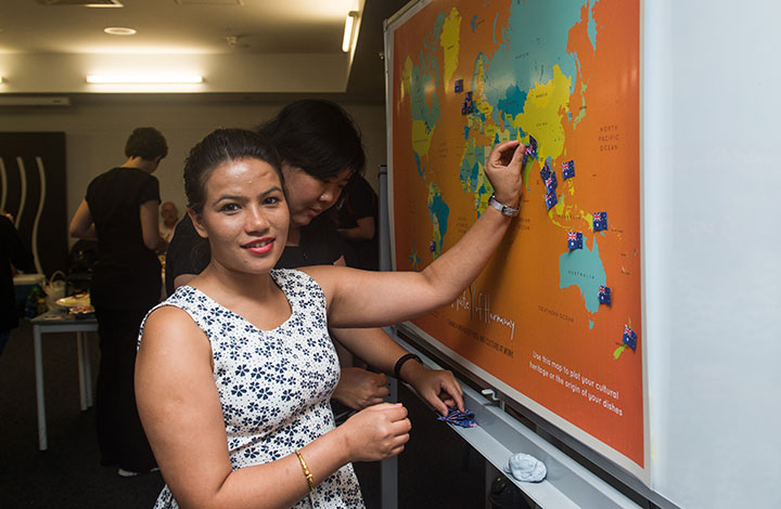 Pashmina Kc places an Australian flag on her home country Nepal, on the World Harmony map