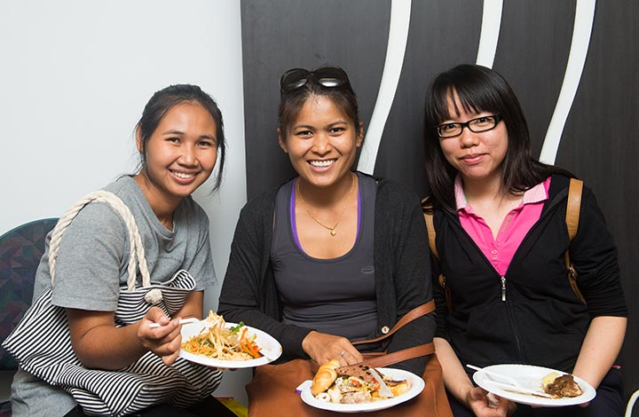 Phongthip Rattiyaporn, Iamon Lomin and Socheata Ith enjoy dishes from around the world at the Harmony Day buffet