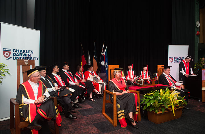 Chancellor Neil Balnaves AO (front left), The Honourable Sally Thomas AC, NT Administrator His Honour The Honourable John Hardy OAM and University Council members on stage as Vice-Chancellor Professor Simon Maddocks welcomes guests.