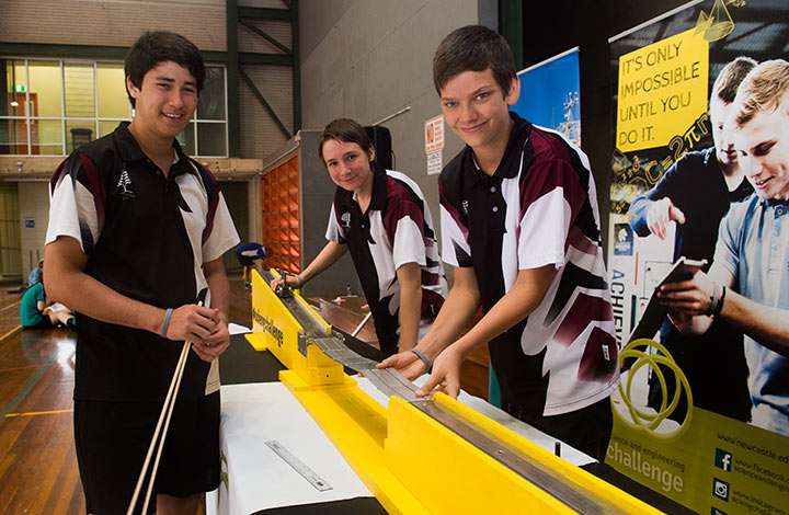 Taminmin College students Reg Whiley, Jordan Mckean and Blake Townsend test the bridge they constructed.