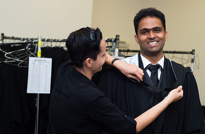 Maria Kammis gowns Ragul Jayabal for the first ceremony in CDU's mid-year graduation ceremonies