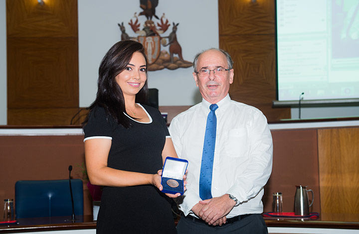 Honourable Acting Chief Justice of the Supreme Court of the NT, Stephen Southwood presents the Supreme Court Medal to student Ann-Marie Najjarin.