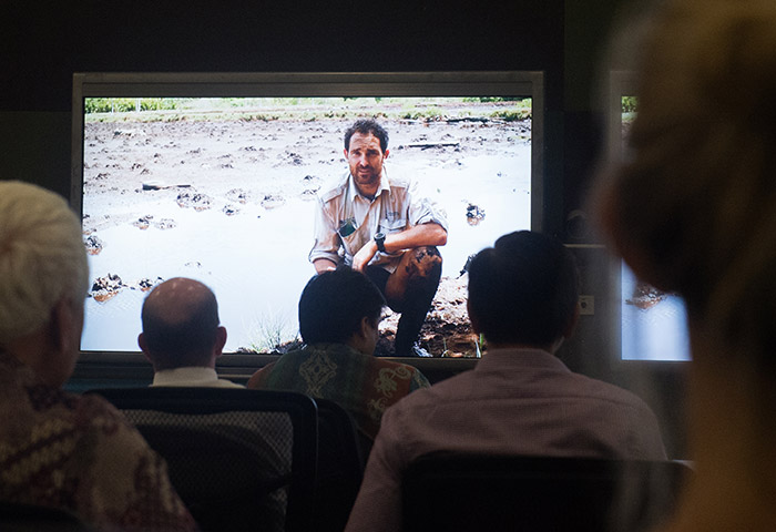 """The crowd watches PhD candidate Clint Cameron on the screen during documentary, """"Taking Stock – Carbon Stock Assessment of Rehabilitated Mangroves in Tiwoho, North Sulawesi"""""""