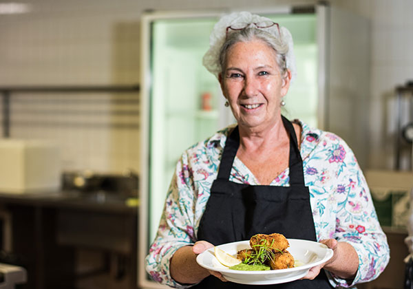 Participant Barbara Laurie with the salmon croquettes she created in class
