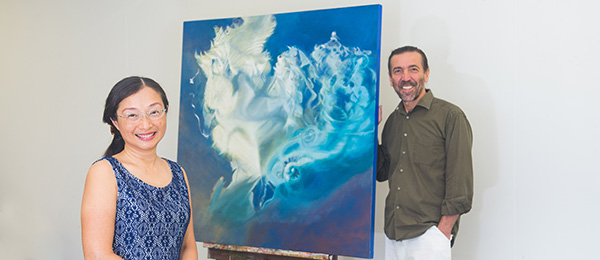 """PhD candidate Isadora Mack with Senior Lecturer in Visual Arts Dr Ioannis Michaloudis and her painting, """"The Spinning Top"""""""