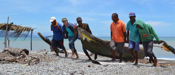 Kim Hunnam in Timor-Leste, helping fishers pull their boats up the beach