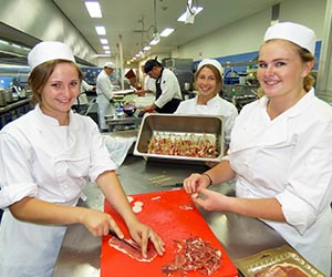 "Kitchen operations students Johanna Ezard, Anina Conradie and Suzi Nitschke prepare scallop prosciutto ""lollipops"" for the degustation menu"