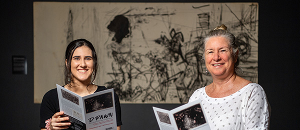 Charles Darwin University Art Collection and Gallery Curator Dr Joanna Barrkman (right) and Bachelor of Arts Honours student Kezia Dilettoso at the latest CDU exhibition, DRAWN from the CDU Art Collection.