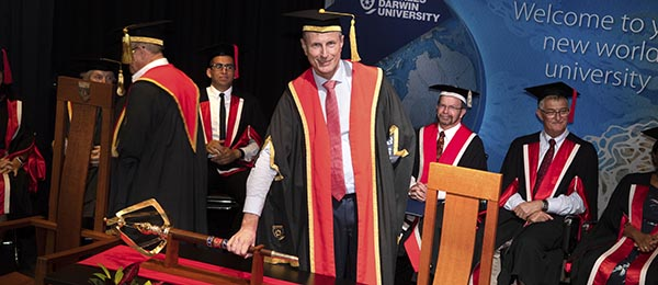 The moment the role of Chancellor of CDU transfers from Mr Neil Balnaves AO to the Hon Paul Henderson AO (centre)