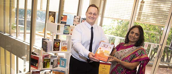 Library Services Director Anthony Hornby receives a literary gift from Indian Consul-General Ms Dantu Charandasi