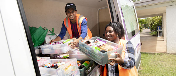 Bachelor of Humanitarian and Community Studies students Tafhim Hussain (left) and Nyasha Matanda distribute food parcels in Palmerston