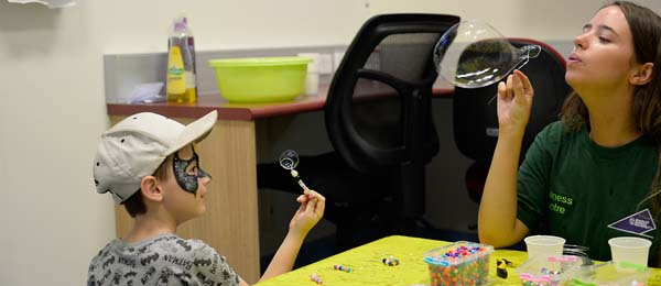 CDU student Meg Pittaway demonstrates to a young participant the technique of blowing bubbles. Image: Michael Prowacki