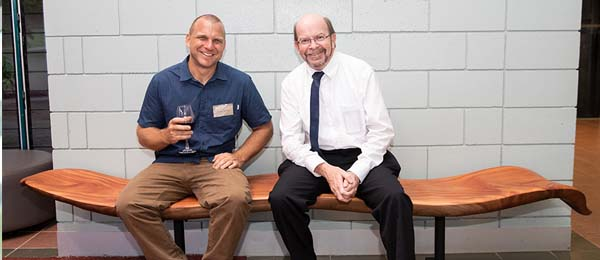 Darwin-based sculptor and CDU Arts alumnus Joel Mitchell and Vice-Chancellor Professor Simon Maddocks on a bench seat based on the seedpod of a native wattle tree