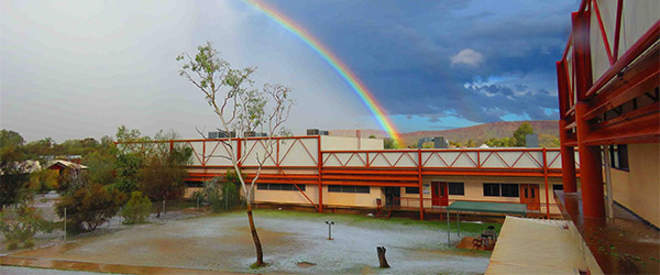 A rainbow over an Alice Springs campus covered in hail