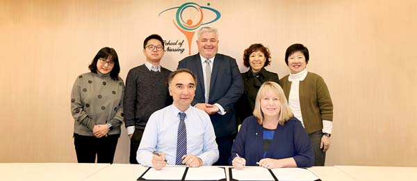 HKPU Head of the School of Nursing Professor Alex Molasiotis (seated left) and CDU's Dean of the College of Nursing and Midwifery Professor Catherine Turner AM (seated right) are working on developing educational exchange opportunities