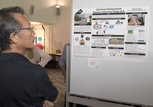 A visitor shows interest in Alwyn Jose's CDU Smart Parking System poster
