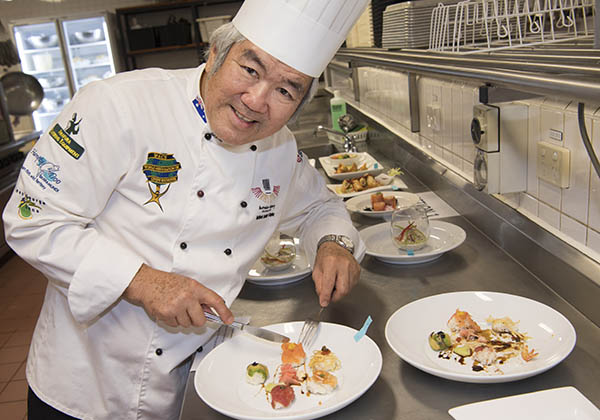 Salon Culinaire coordinator T.Y. Lee judges the hot and cold entrees