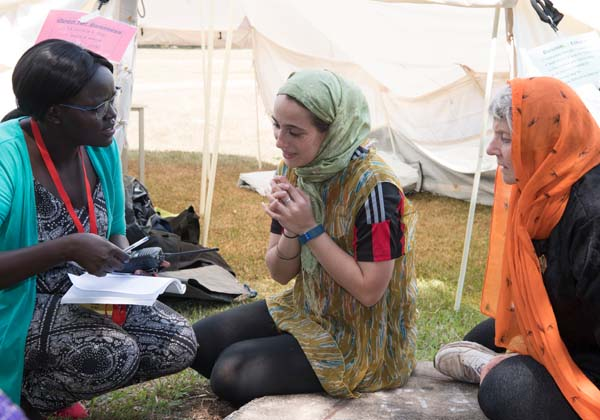 Student Helen Ojaba, a community liaison for fictional aid provider Red Heart, explains a situation to Jesspreet Kaur and Karen Dempsey