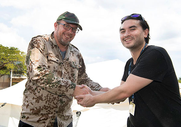 Sebedoh Army Brigadier Uzi Umbala (aka RedR trainer Ulf Edqvist) and student Tristan Salim, in the role of UN country coordinator, shake on an agreement about aid services
